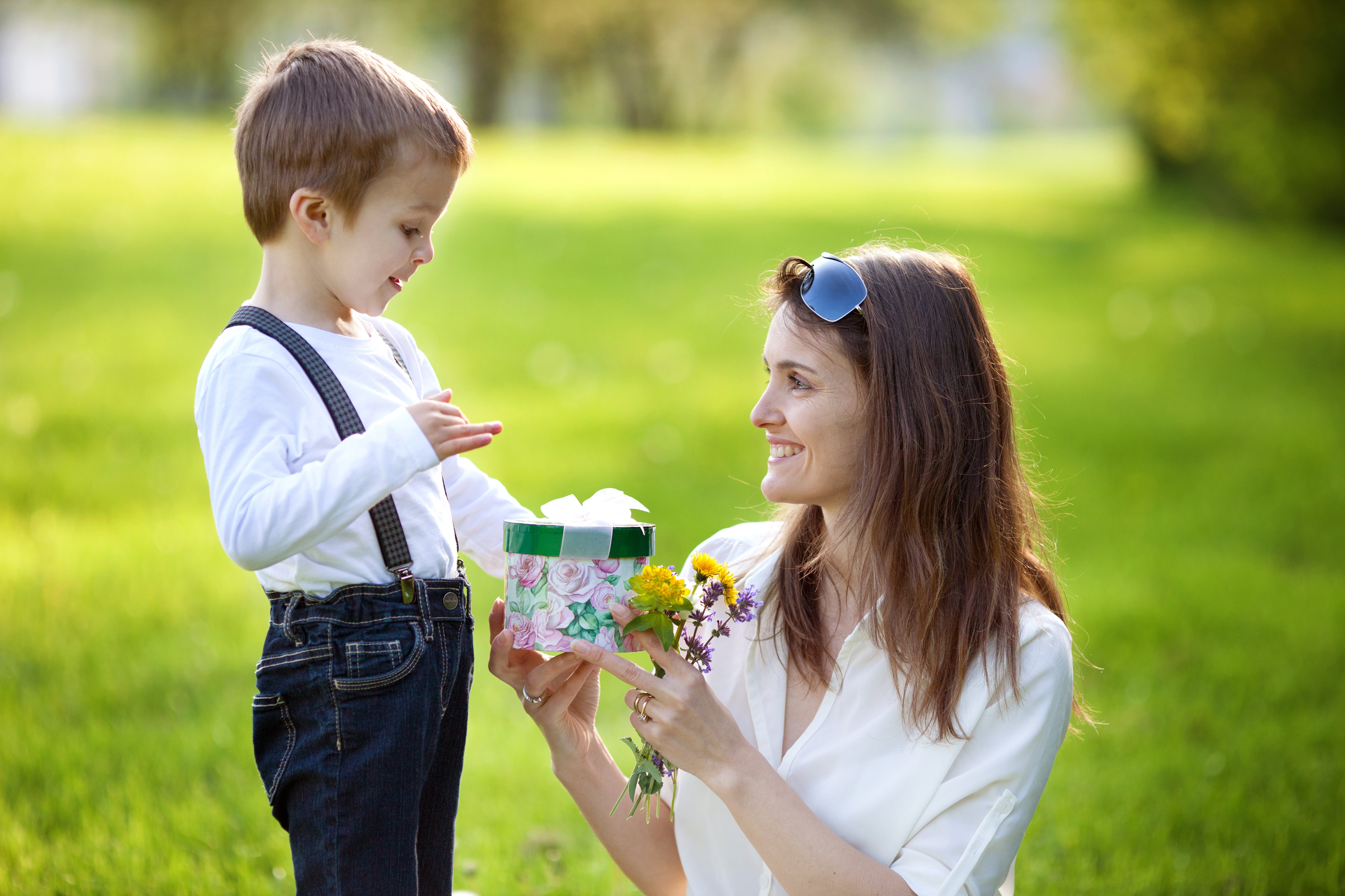 Beautiful kid and mom in spring park, flower and present. Mothers day celebration concept